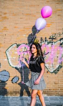 Girl, tenue, ballons, devant, mur graffiti