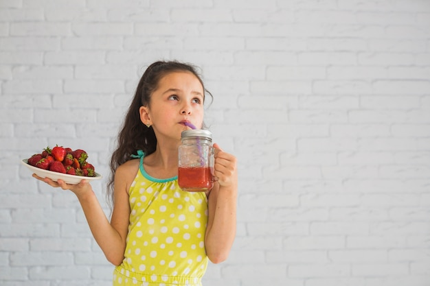 Girl, tenue, plaque, de, fraises rouges, boire, fraises, smoothies
