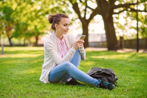 Girl using mobile phone app texting sms ou en naviguant sur les réseaux sociaux en ligne