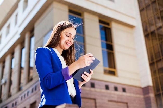 Girl vérifie sa tablette debout dans la rue