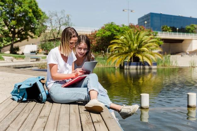 Girlfriends à l'aide de tablette sur le parc avec lac