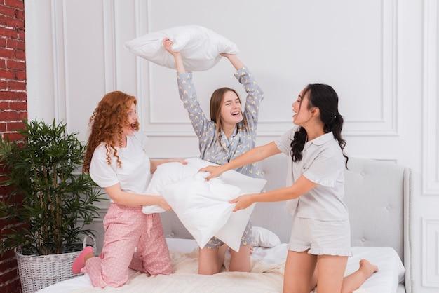 Girlfriends se battre avec des oreillers