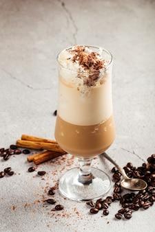 Glace au café dans un verre sur le fond de béton décoré de haricots et de cannelle