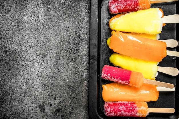 Glace aux fruits multicolores à base de fruits. sur un fond rustique.