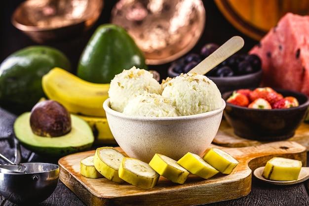 Glace à la banane maison et végétalienne sans lait dans un bol en plastique recyclé, avec des fruits en arrière-plan