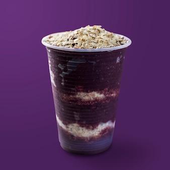 Glace congelée brésilienne et aux baies d'açai sur une tasse en plastique avec des flocons d'avoine. isolé sur fond violet. vue de face du menu d'été.