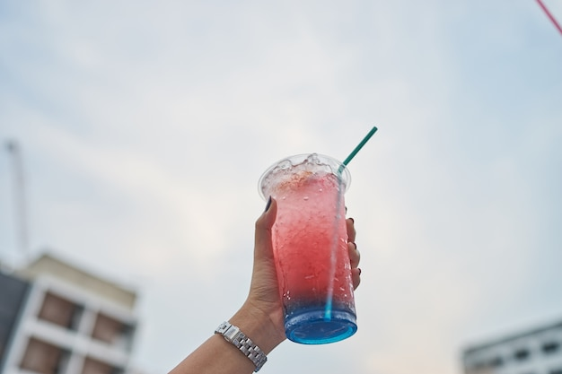 Glace douce douce soda coloré brillant sur la main de l'asiat