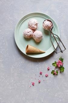 Glace fraîche et froide dans la plaque verte avec des fleurs roses sur la table grise. vue de dessus
