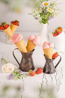 Glace à la fraise dans des tasses à gaufres sur fond de bois blanc