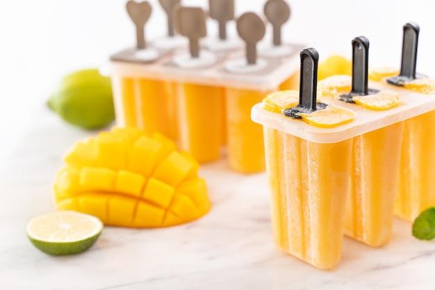 Glace glacée aux fruits à la mangue fraîche dans la boîte de mise en forme en plastique sur une table en marbre brillant