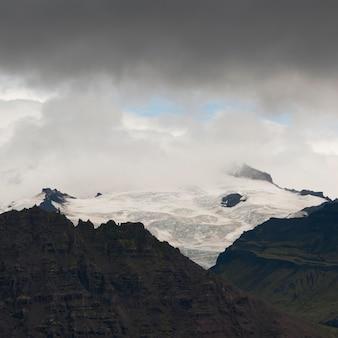 Glace glaciaire sur la montagne déchiquetée, entourée de nuages