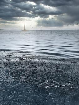 Glace d'hiver bleue - une scène d'hiver avec de la glace bleue avec un phare brillant au loin, sur fond de beaux nuages couverts.