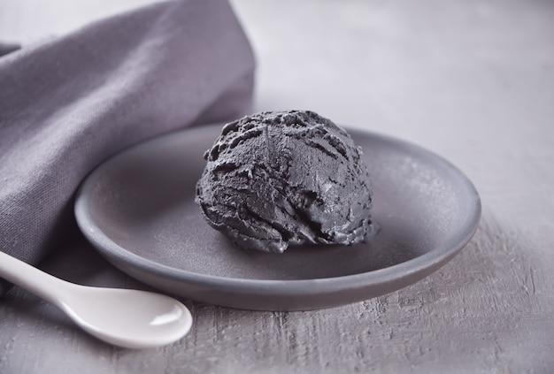 Glace noire sur une plaque en céramique noire avec une serviette grise sur une table grise
