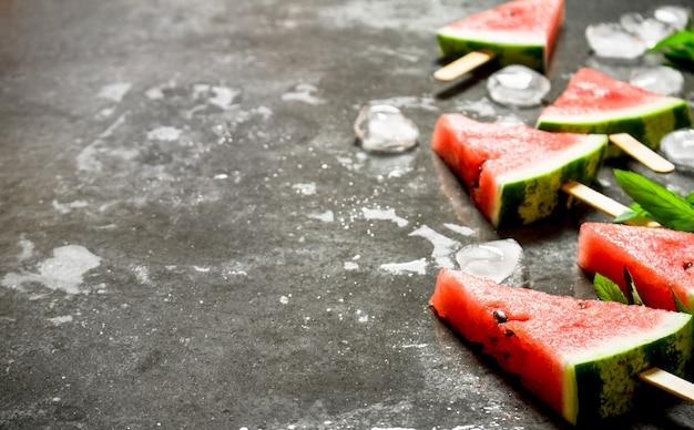 Glace à la pastèque sur des bâtons en bois sur la table en pierre
