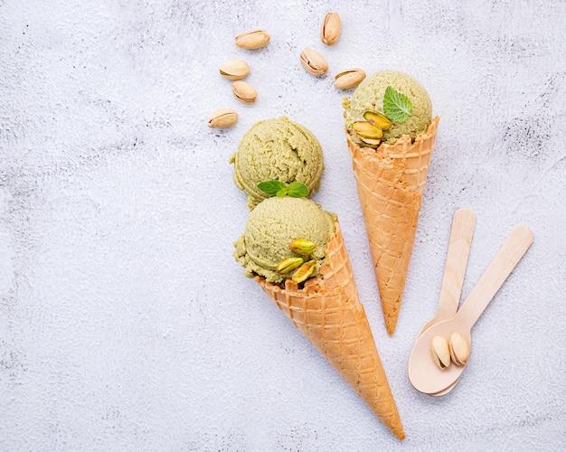 Glace à la pistache en cônes avec configuration de pistaches sur fond de pierre blanche.