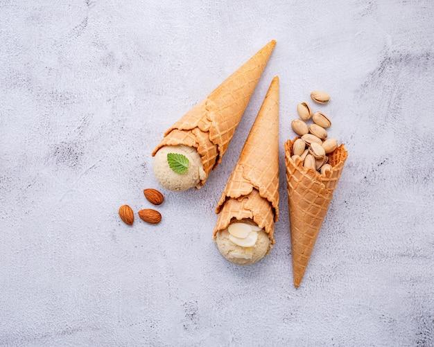 Glace à la pistache et à la vanille en cônes avec configuration de noix mélangées sur fond de pierre blanche