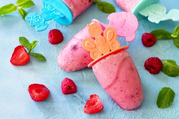 Glace pour enfants popsicles fraise-framboise sorbet sur fond de béton bleu