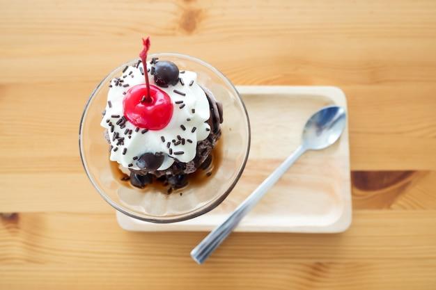 Glace sundae au chocolat servie avec de la crème fouettée et de la cerise sur le dessus.