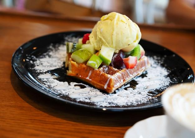 Glace à la vanille avec des baies, des fraises, des framboises, des pommes sur des gaufres avec du sucre en poudre