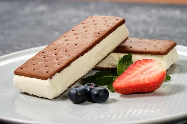 Glace vanille avec des biscuits sur une assiette blanche avec des baies