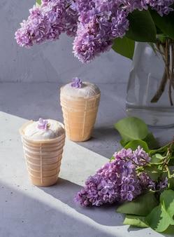 Glace à la vanille dans une tasse à gaufres avec des fleurs lilas sur fond gris