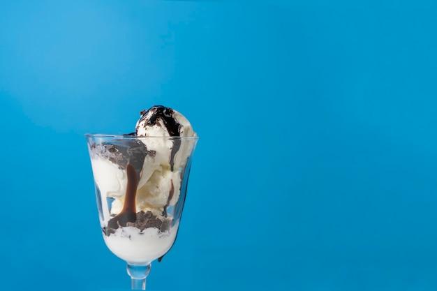 Glace à la vanille versée avec du chocolat vivant. dessert d'été appétissant sur fond bleu