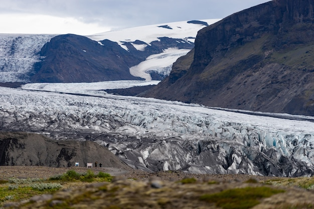 Glacier avec des cendres dans la glace avec de l'eau fondue et paysage islandais