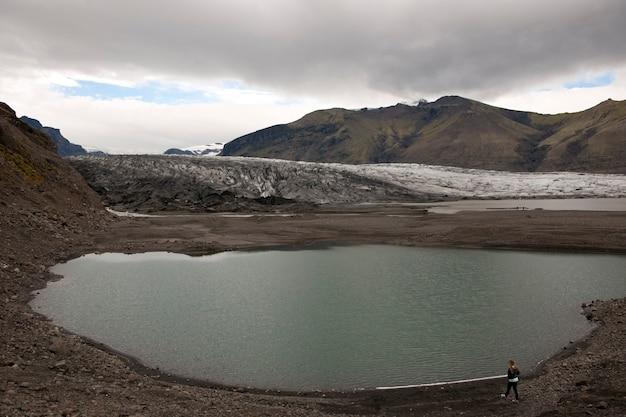Glacier et lac glaciaire entouré de montagnes par temps nuageux