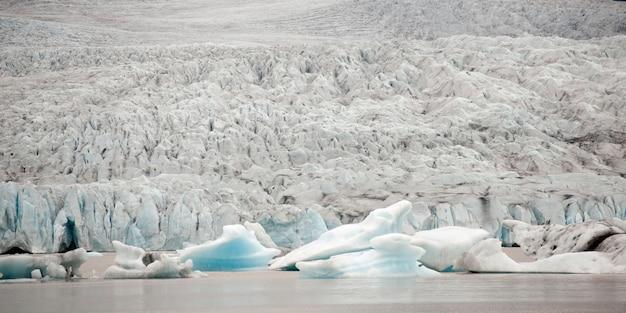 Glacier rencontrant l'océan et les icebergs flottant