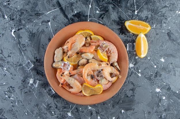 Glaçon, citrons tranchés et crevettes sur une assiette à côté d'un bol de sel, sur la surface en marbre.