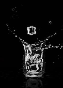 Glaçon tombant dans un verre et éclaboussures d'eau sur fond noir