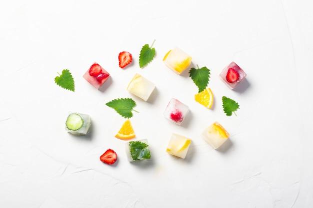 Glaçons aux fruits et feuilles de menthe sur fond de pierre blanche. concept de glace aux fruits, étancher la soif, l'été. mise à plat, vue de dessus