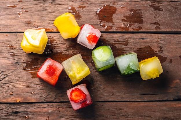 Glaçons aux fruits sur table en bois. le concept de dessert chaud d'été. mise à plat, vue de dessus