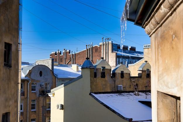 Glaçons contre le ciel bleu et les toits couverts de neige