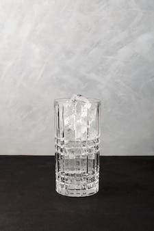 Glaçons dans un grand verre à cocktail. fond gris, copiez l'espace. de la vraie glace transparente pour des boissons rafraîchissantes.