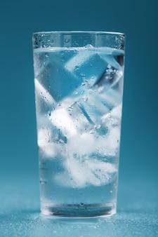 Glaçons dans un verre d'eau cristalline sur fond bleu.
