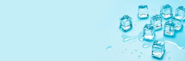 Glaçons avec de l'eau sur fond bleu. concept de glace pour les boissons. bannière