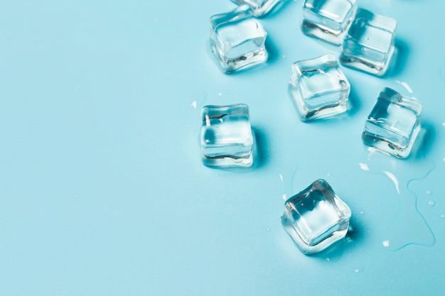Glaçons avec de l'eau sur fond bleu. concept de glace pour les boissons.