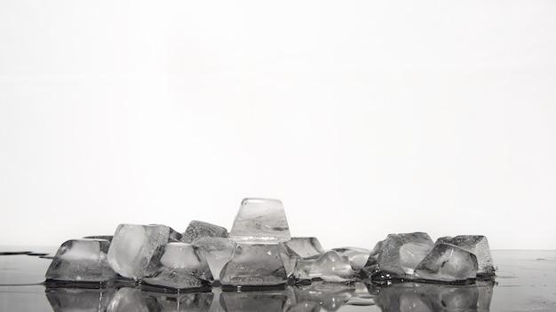 Glaçons fondant sur une surface réfléchissante sombre, fond blanc, mise au point sélective.