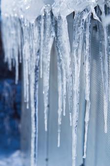 Les glaçons fondent. dégel printanier. hiver chaud . les glaçons se bouchent. gros plan d'un grand glaçon ondulé avec plus de glaçons fondants à côté et un fond d'hiver doux.