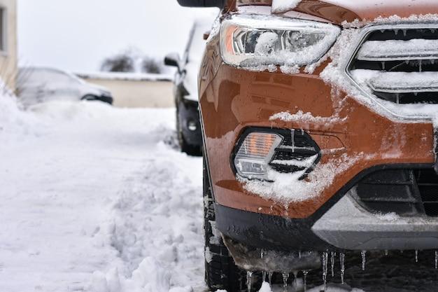 Des glaçons pendent au capot de la voiture en hiver