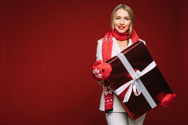Gladsome jeune femme en costume élégant et mitaines tenant une grande boîte-cadeau de noël et regardant la caméra. concept de vacances