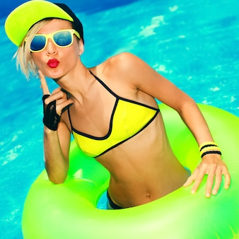 Glamorous fashion girl dans un style de fête d'été chaud à la piscine