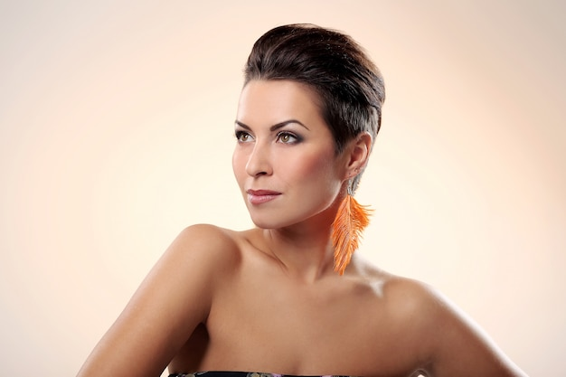 Glamour and magnifique brunette avec boucle d'oreille de plume
