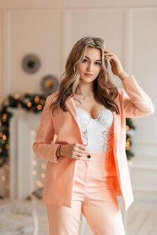 Glamour belle jeune femme chaude avec de beaux seins sexy dans un costume à la mode et un blazer avec body en dentelle sur fond de lumières jaunes à l'intérieur