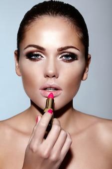 Glamour closeup portrait of beautiful sexy caucasian brunette young woman model appliquer le maquillage rouge à lèvres sur ses lèvres avec une peau parfaitement propre