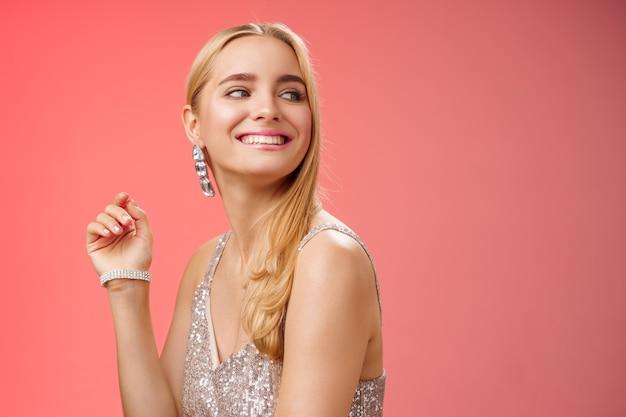 Glamour élégant magnifique jeune femme blonde riche assister à une fête de charité dans une élégante robe scintillante argentée accessoiriser en tournant à droite souriant salutation personne familière souriant joyeusement, fond rouge