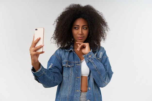 Glamour femme à la peau foncée bouclée en haut blanc et manteau en jean touchant doucement son menton tout en faisant une photo d'elle avec un smartphone, posant sur un mur blanc