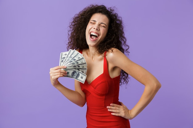 Glamour femme vêtue d'une robe rouge souriant et tenant un ventilateur d'argent, debout isolé sur mur violet