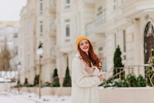 Glamour fille aux cheveux longs posant sur la rue flou. modèle féminin attrayant aux cheveux roux profitant de l'hiver.
